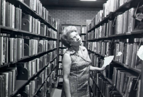 Mrs. Lee poses in the stacks at the Richard B. Harrison Library on New Bern Ave.