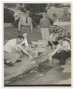 Officers in Spray pour illegal whiskey down the storm drain in the 1950s.
