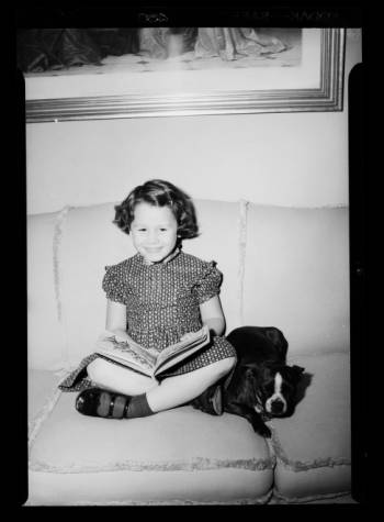 Young_Girl_Sits_with_Picture_Book_and_Dog