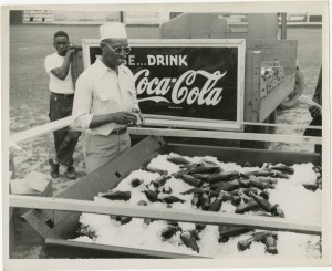 Man standing by an iced cart of Coca-Cola