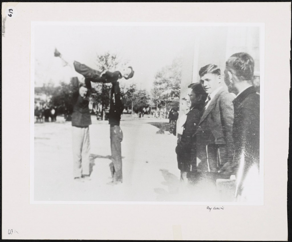 A group of boys watches as two boys lift a third into the air over their heads