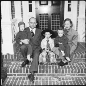family_poses_for_christmas_picture_on_steps