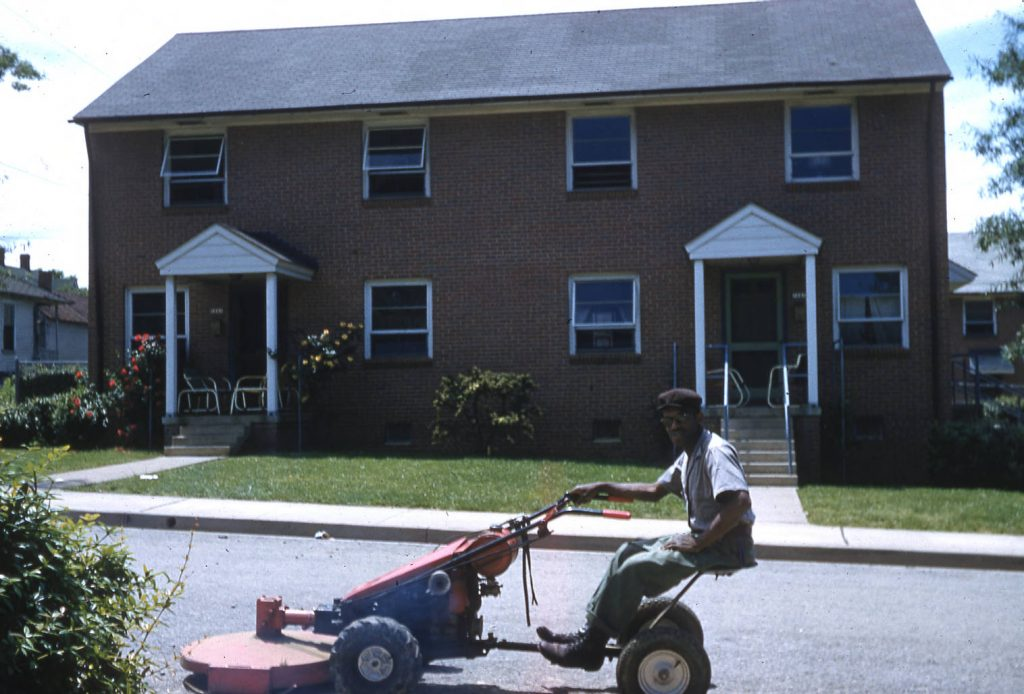 Man on lawn mower in front of homes on Cleveland Ave. Winston Salem