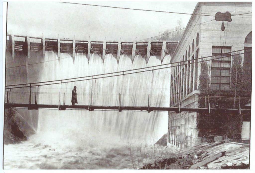 Man on a bridge in front of a dam