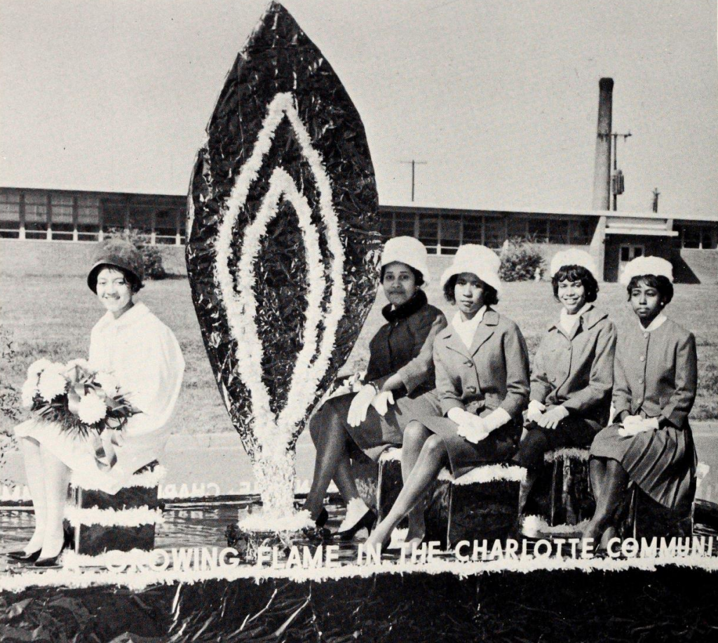"Five women seated on a float that says ""A growing flame in the Charlotte Communi[ty]"""