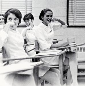 nurses seated at desks miming brushing teeth