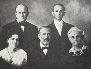 group portrait with two people in back wearing suits, and three people in front, two in dresses and one in a suit
