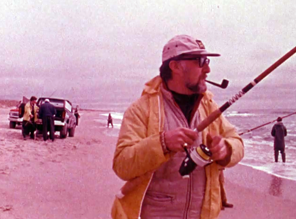 Man in a yellow slicker fishing on the beach, smoking a pipe