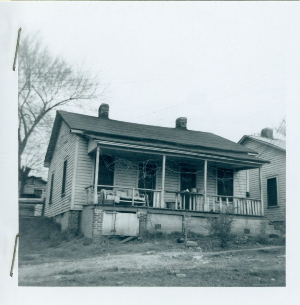 Black and white photograph of a house with a porch