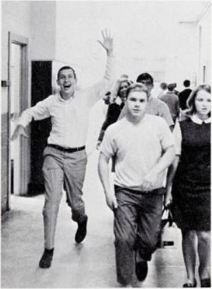A student waves in a high school hallway.