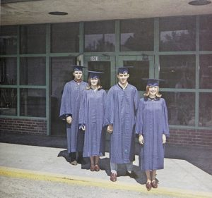 Four graduates in caps and gowns standing in front of a door