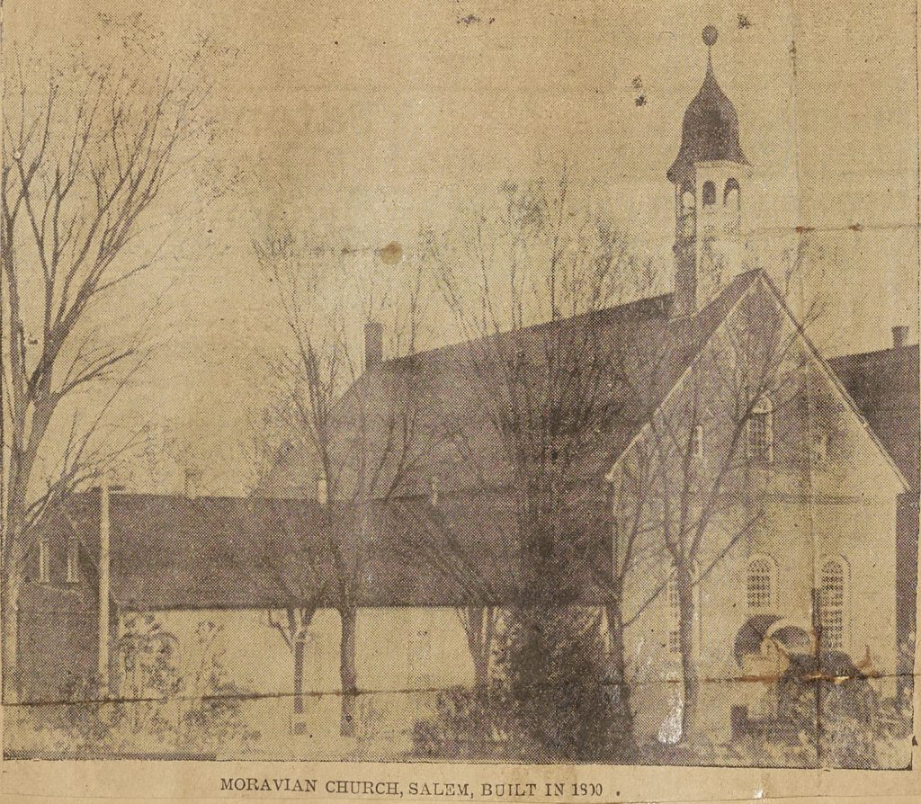 newspaper clipping of black and white photo of moravian church behind trees