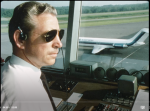 air traffic controller in tower with view of tarmac and plane