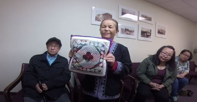 Chia Yang shows a pillow from her home in Vietnam during oral history interview.