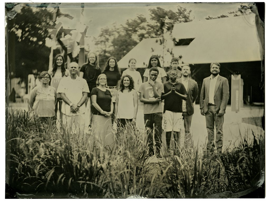 Group portrait of middle schoolers and adults outside in a field