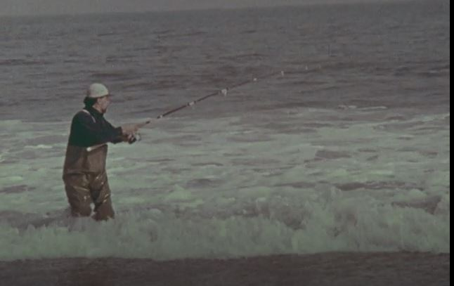 Man standing in the ocean holding a fishing pole