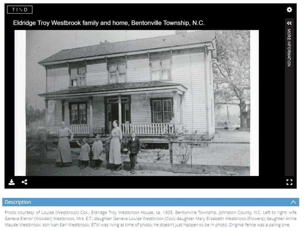 Black and white photo of five family members standing in front of a house.