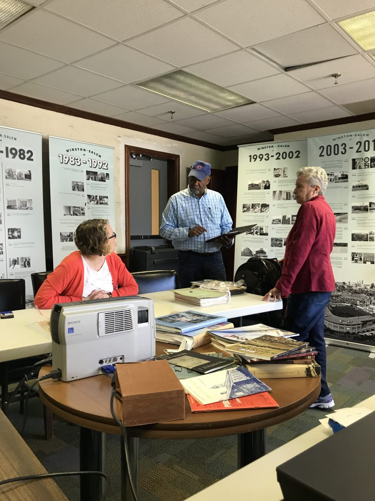 Three people talking around a table of archival materials