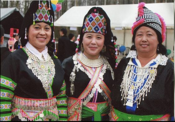 color image of three individuals facing camera and smiling, in traditional Hmong dress