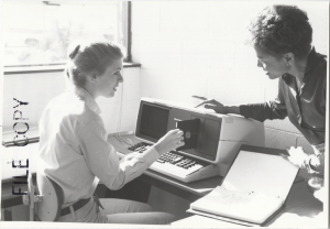 Woman seated before a computer while instructor bends close and points to floppy disk
