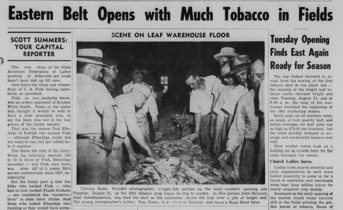 "Article in The Zebulon Record titled ""Eastern Belt Opens With Much Tobacco In Fields"" accompanied by a photo of farmers gathering around tobacco leaves."