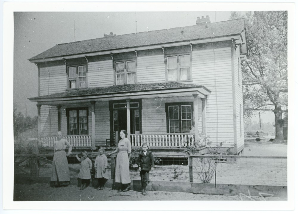 Photo of the Westbrook House, ca. 1905, with four family members standing in front of the house. Left to right: Geneva Elenor (Woodall) Westbrook (wife of Eldridge Troy Westbrook); Geneva Louise Westbrook (Cox) (daughter); Mary Elizabeth Westbrook (Flowers) (daughter); Annie Maude Westbrook (daughter); Ivan Earl Westbrook (son).