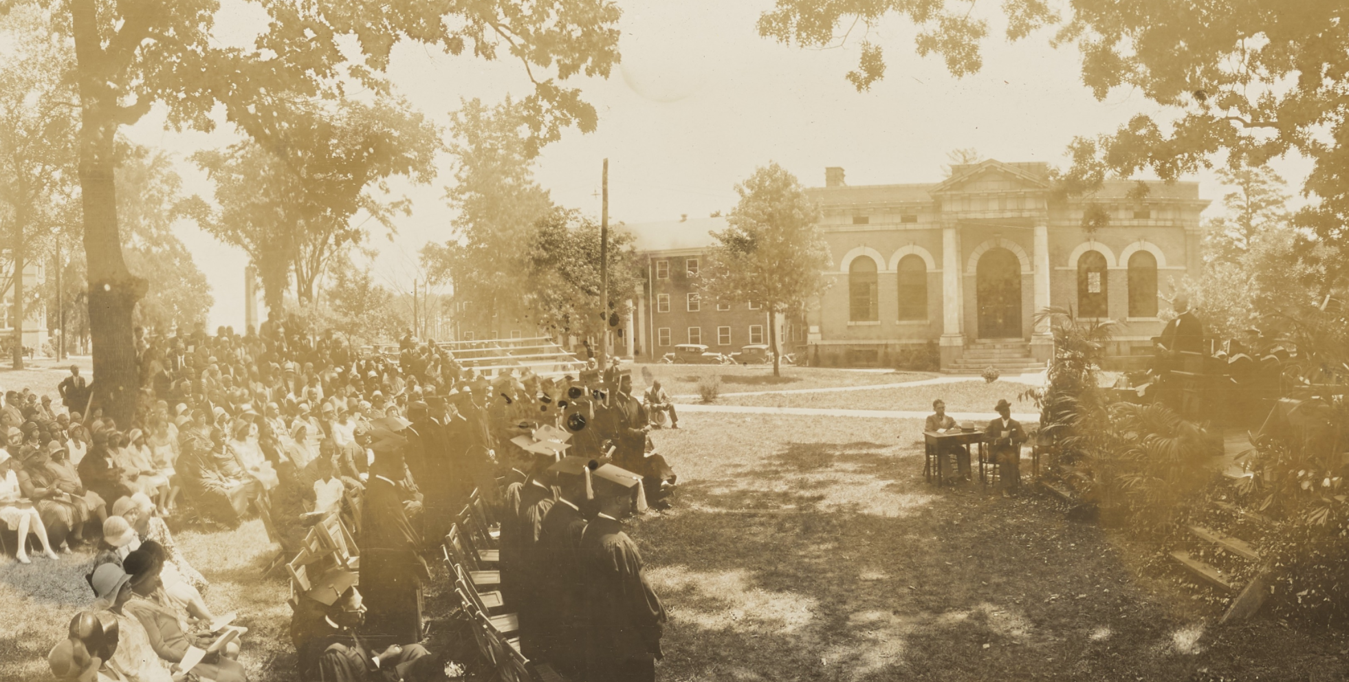 Cropped image of a commencement ceremony at Biddle University in the 1920s. The photo depicts the family and friends watching the commencement speaker. The photo was taken outdoors at Johnson C. Smith University grounds.
