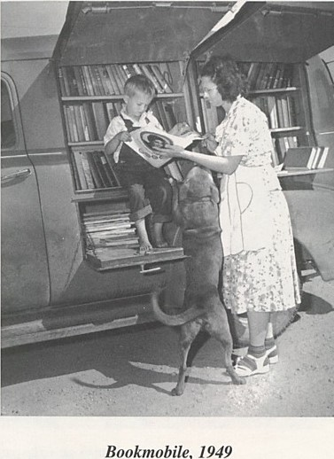 Family and their dog looking at books in the library's bookmobile.