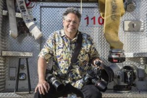 Smiling individual seated on rear of fire truck with multiple cameras in hand
