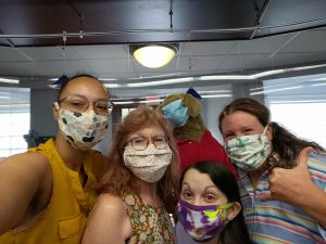 Four individual taking a selfie with a stuffed toy dog, all wearing masks