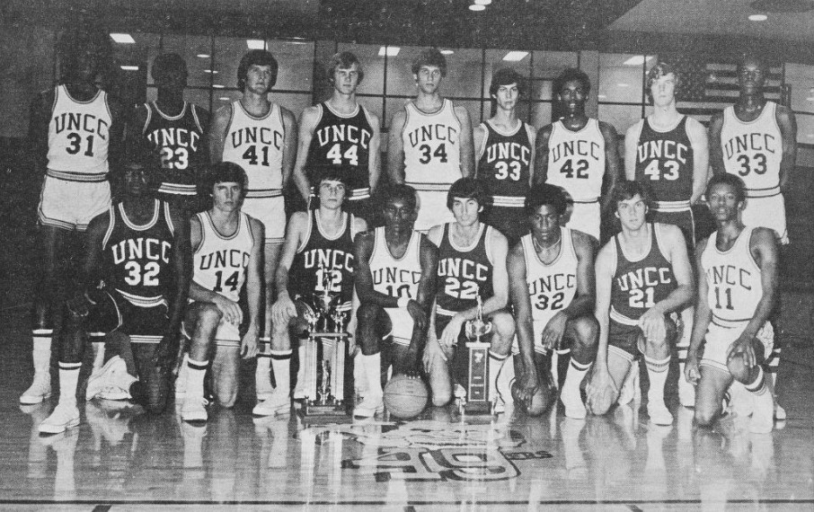 Cropped image of the UNCC 49ers 1974 basketball team posing for a photo on the court with their trophy.
