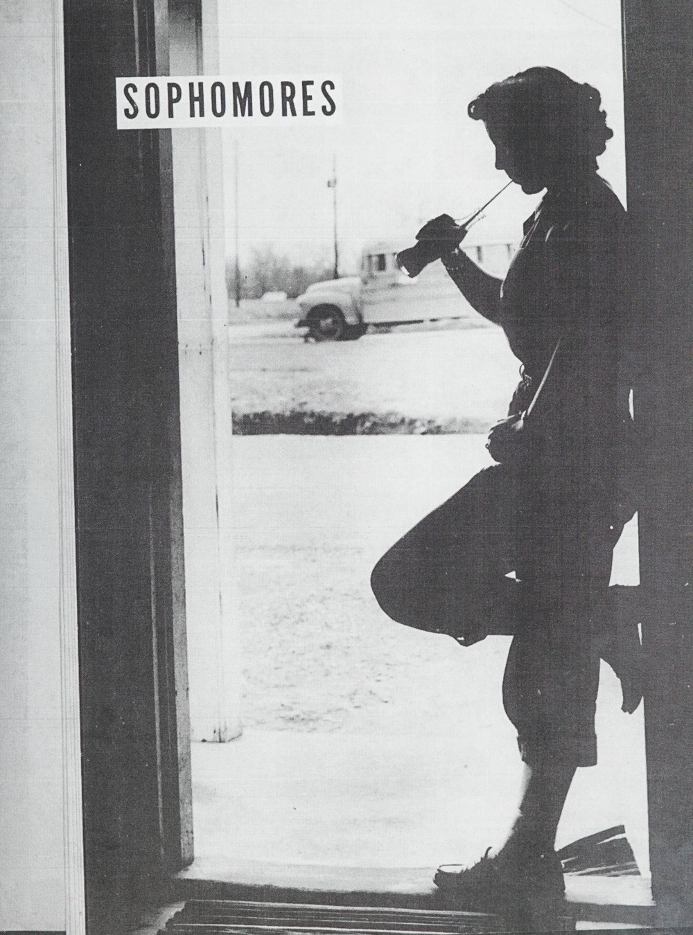 "Person standing in a doorway drinking from a glass Coke bottle with a straw. ""Sophomores"" is written in the top left."