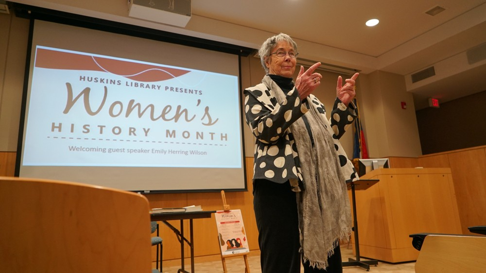 "Emily Herring Wilson speaking at Rotary Auditorium in the J.P. and Mildred Huskins Library. She is standing to the right, pointing with both hands towards the audience. Behind her is a projection that reads ""Women's History Month""."