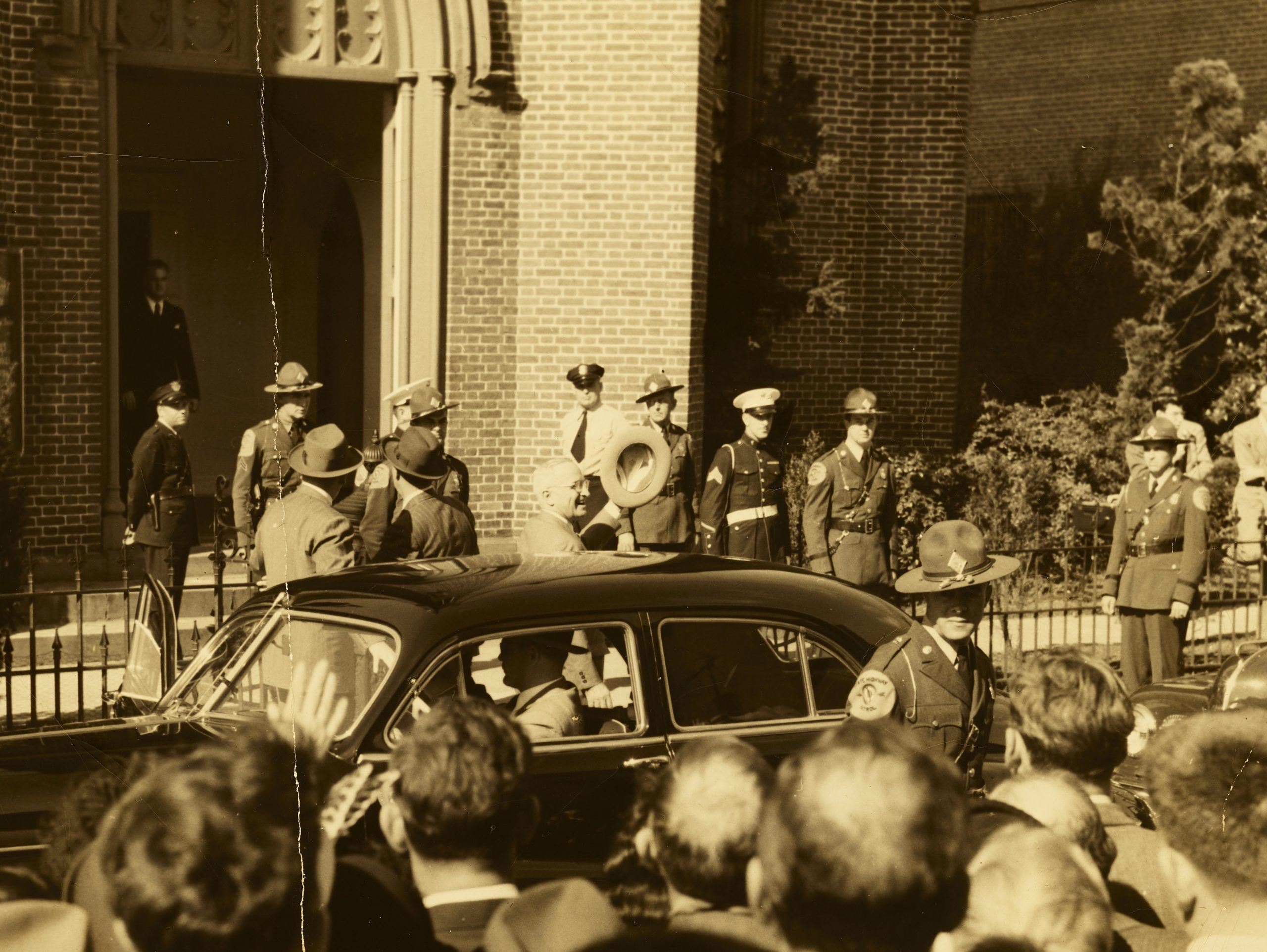 Picture of Harry Truman leaving the First Baptist Church. He is holding his hat in the air about to get into a car. There is a crowd of people around the car.