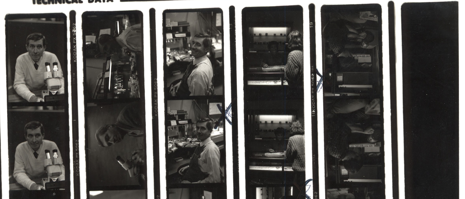 Close up crop of a black and white contact print of Baum Jewelry Craftsmen employees working in the store.