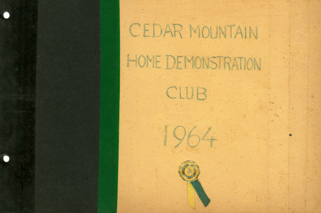"""Clipping of the cover of a scrapbook. It has a black and cream cover with a green stripe and green writing. It reads, """"Cedar Mountain Home Demonstration Club 1964"""". There is also a small medal with a yellow and green ribbon."""