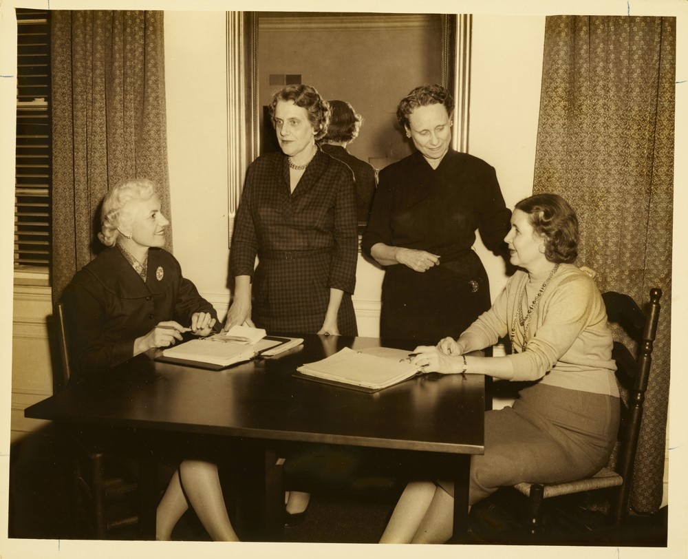 Four women sitting around a table talking to one another.