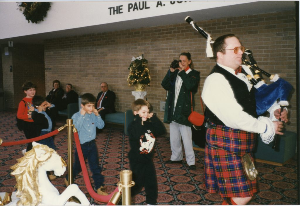 Photo of a bagpipe player with kilt on playing the bagpipe. The musician is walking to the right while three children walk behind the musician, covering their ears.