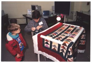 An older adult demonstrates a quilting technique during a Johnston Community College Open House.
