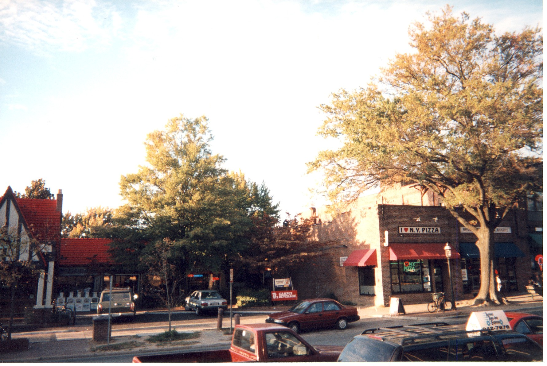 Photo taken on a sunny, fall day from the opposite side of the street of several shops on West Franklin Street, Chapel Hill, North Carolina. I Love N.Y. Pizza and TJ's Campus Beverage are visible.