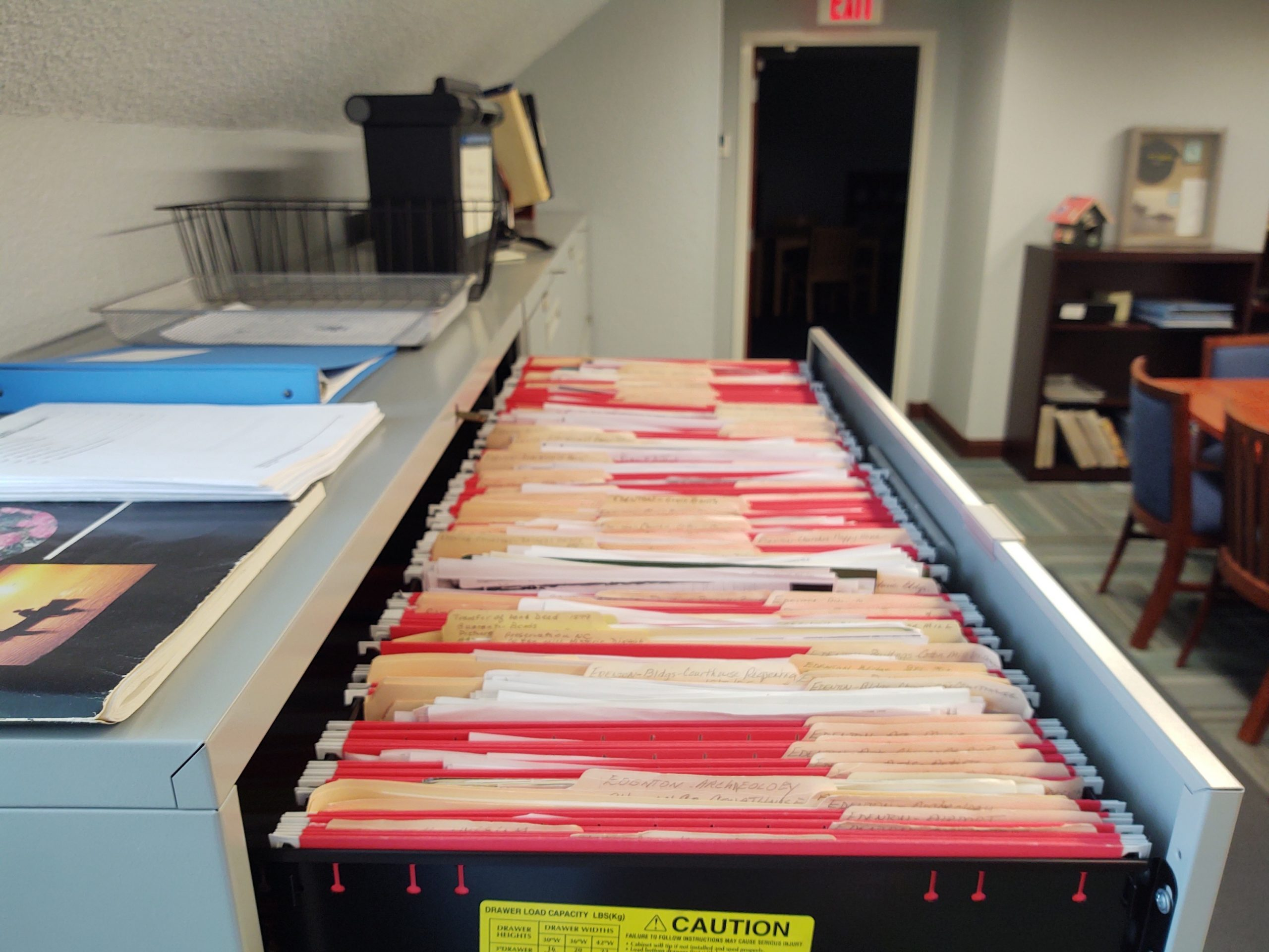 Long, open filing cabinet drawer filled with red and manilla files