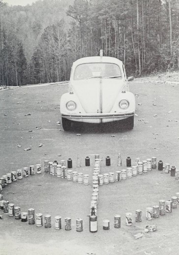 A Volkswagen Beetle is parked behind beer and liquor bottles shaped into a peace sign.