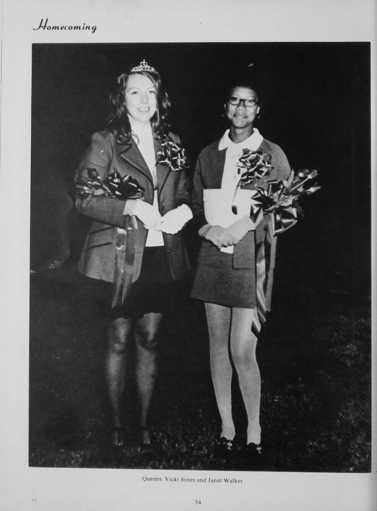 Homecoming queens Vicki Jones and Janet Walker standing next to each other with flowers in their arms.