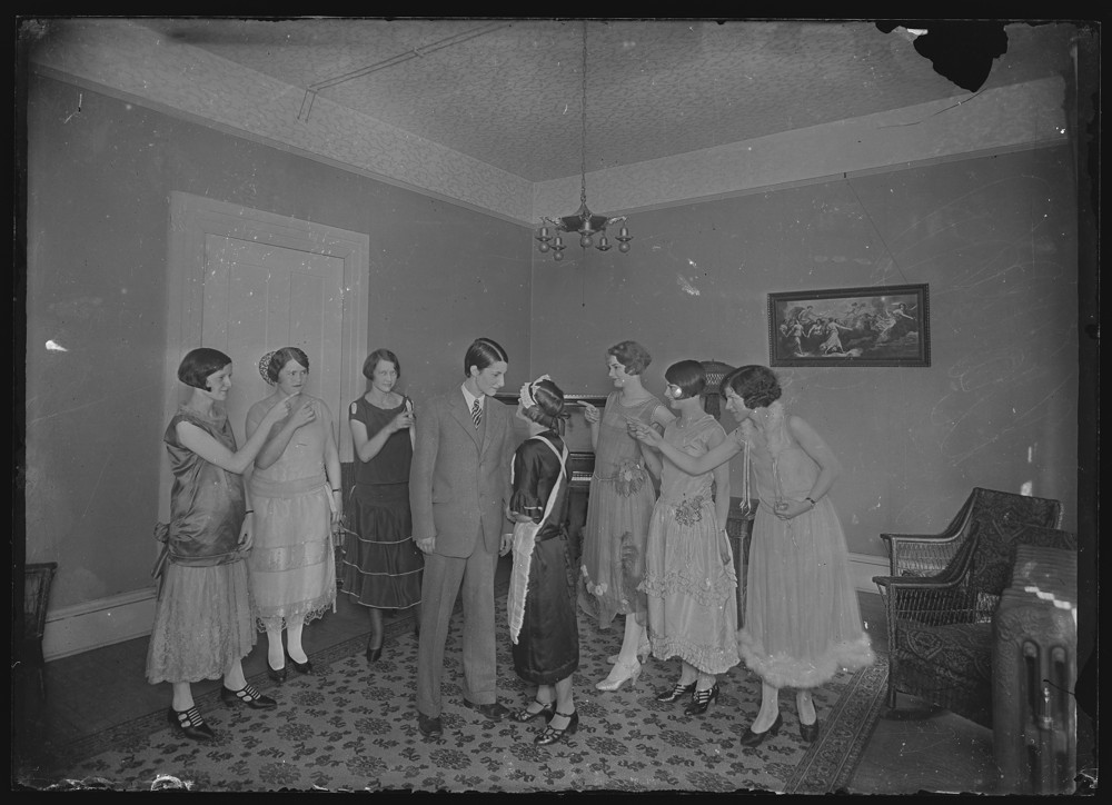 Group of students in dresses pointing at two students, one in a suit and one in a maid costume