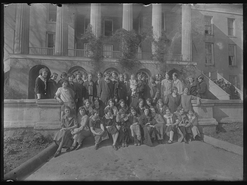Black and white photograph of students outside a building