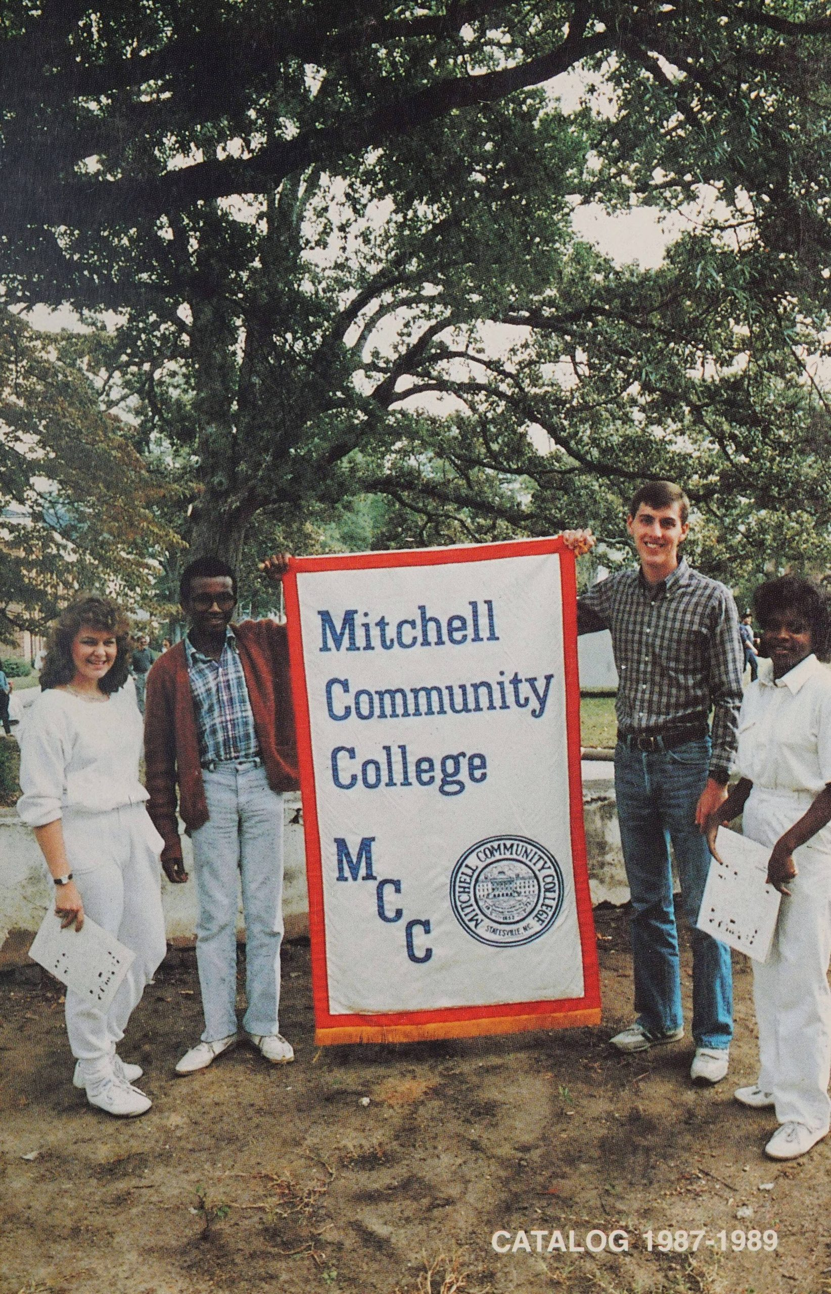 """A group of students standing beside a banner that reads """"Mitchell Community College; MCC."""""""