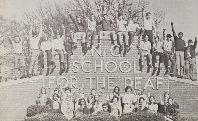 A group of students gather around the brick sign for N.C. School of the Deaf to pose for a photo.