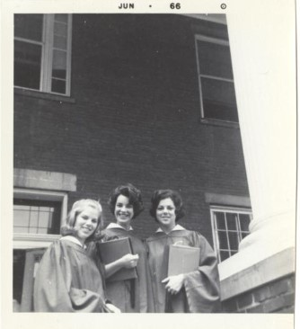 A black and white photo of three smiling students in graduation attire posed in front of a building.