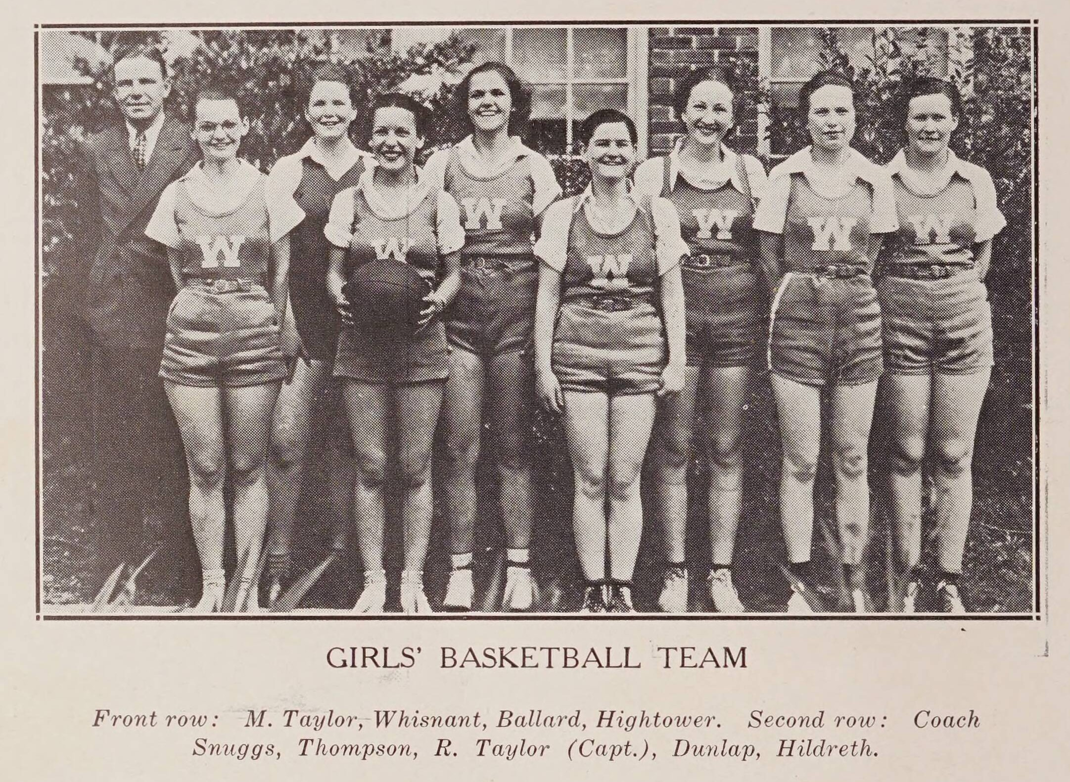 Wadesboro HS 1936 women's basketball team. Eight women lined up in their basketball uniforms. The coach, Coach Snuggs, is on the left.