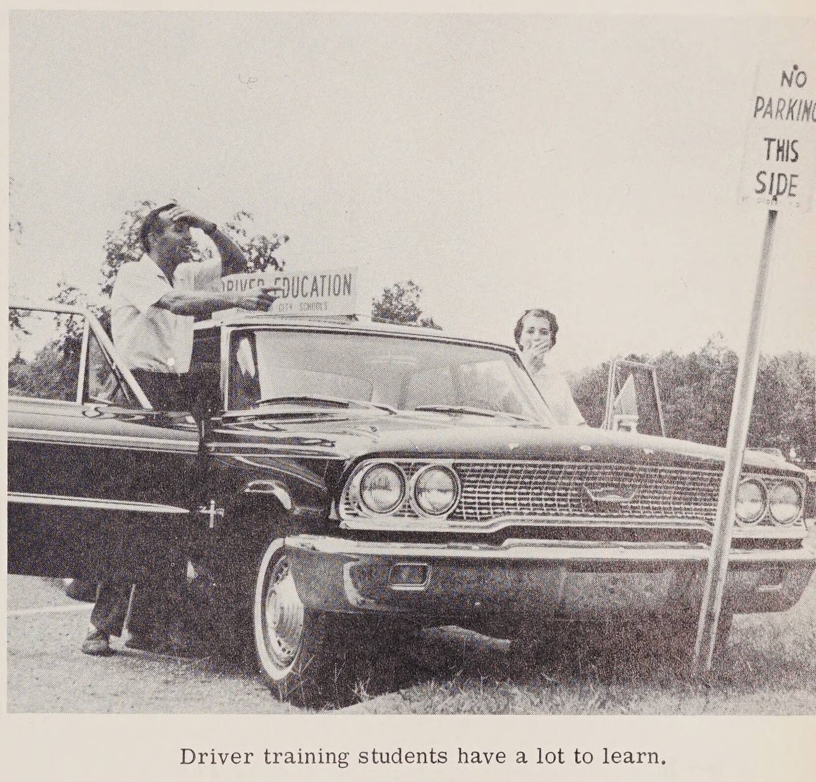 """Two individuals standing at the doors of a driver education car. The car is posed to look like it has hit a sign. The caption on the image reads """"Driver training students have a lot to learn."""""""